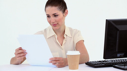 Female worker reading a file at her desk Stock Video Footage