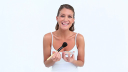 Laughing woman applying blush on her face Stock Video Footage