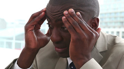 Black man in suit massaging his forehead Footage