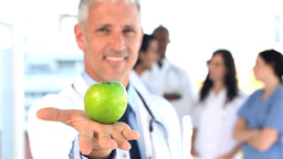Smiling practitioner showing a green apple Footage