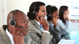 Happy call centre agents talking with their headse Stock Video Footage