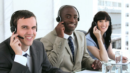 Smiling call centre agents working with headsets Footage