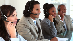Happy call centre agents wearing headsets Stock Video Footage