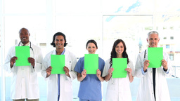 Smiling medical team showing blank papers Footage