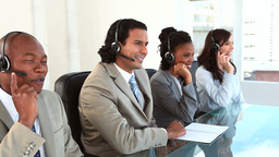 Happy call centre agents working with headsets Footage