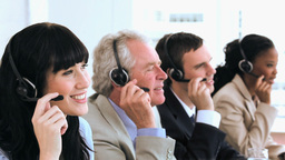 Joyful call centre agents sitting while wearing he Footage