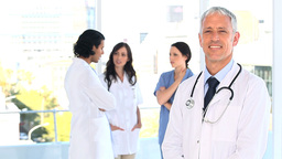 Smiling mature doctor standing upright in front of Footage