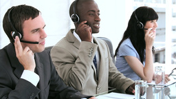 Happy call centre agents working together with hea Stock Video Footage