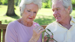 Retired woman smelling a rose with her husband Live Action