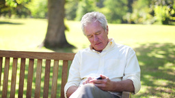 Retired man using a mobile while sitting on a benc Footage