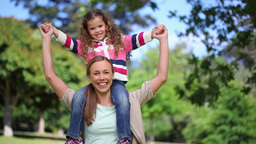 Woman turning with her daughter on her shoulders Footage