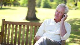 Retired man using a mobile phone on a bench Stock Video Footage