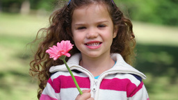 Little girl showing a pink flower Footage