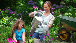 Mother watering flowers while her daughter is watc Footage