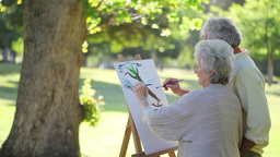 Retired people painting a tree together Footage