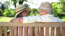 Mature couple wearing hats kissing on a bench Footage
