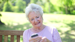 Retired woman using a mobile phone Footage