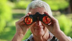 Smiling mature man looking through binoculars Footage