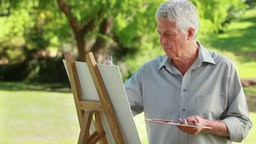 Smiling mature man drawing on a canvas Stock Video Footage
