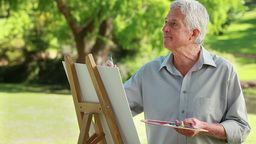 Smiling mature man drawing on a canvas Footage