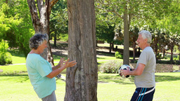 Smiling mature couple playing with a soccer ball Footage