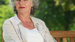 Smiling mature woman sitting on a wooden bench Footage