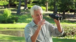 Retired couple looking through binoculars Stock Video Footage