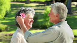 Smiling mature man giving a flower to his wife Stock Video Footage