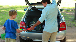 Father and son placing things in the trunk of the Stock Video Footage
