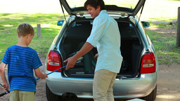 Father and son placing things in the trunk of the  Footage