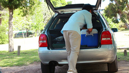 Rear view of a man placing his cooler in his car Footage