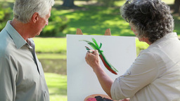 Mature Man Looking At The Canvas Of Her Wife stock footage