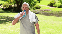 Happy mature man drinking water while standing upr Footage