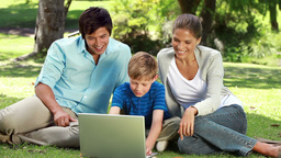 Happy family looking at a laptop while sitting on Stock Video Footage