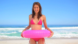 Cheerful brunette woman holding an inflatable rubb Footage
