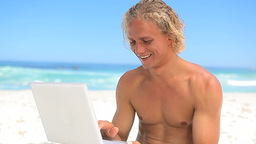 Smiling blonde man holding a laptop Footage