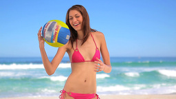 Happy brunette woman playing with a beach ball Stock Video Footage