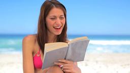 Smiling brunette reading an interesting novel Footage