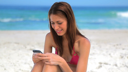 Happy brunette sitting on the sand while using her Footage