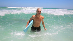 Blonde man walking while holding his surfboard Stock Video Footage