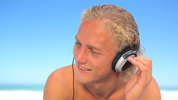 Blonde man listening to music with headphones Footage