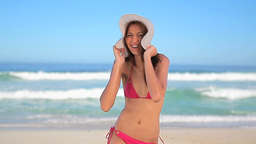Happy brunette woman placing a hat on her head Stock Video Footage