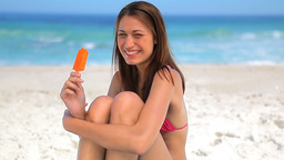 Cheerful woman eating an orange ice lolly Footage
