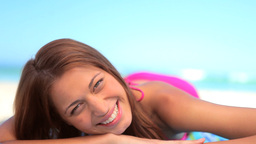 Happy brunette woman lying on her towel Stock Video Footage