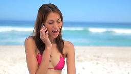 Happy brunette woman talking on the phone on the b Stock Video Footage