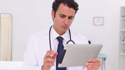 Serious doctor using a touchscreen Stock Video Footage