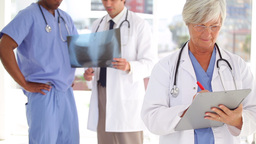 Serious doctor writing on a clipboard in front of Stock Video Footage