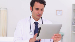 Serious doctor using his tablet pc Stock Video Footage