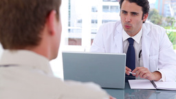 Blackhaired doctor talking with his patient Footage