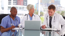 Mature doctor talking with two colleagues Stock Video Footage